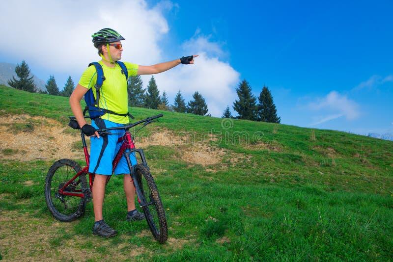 Un jeune homme couvertures extérieures de monte d'un vélo de montagne le chemin images libres de droits