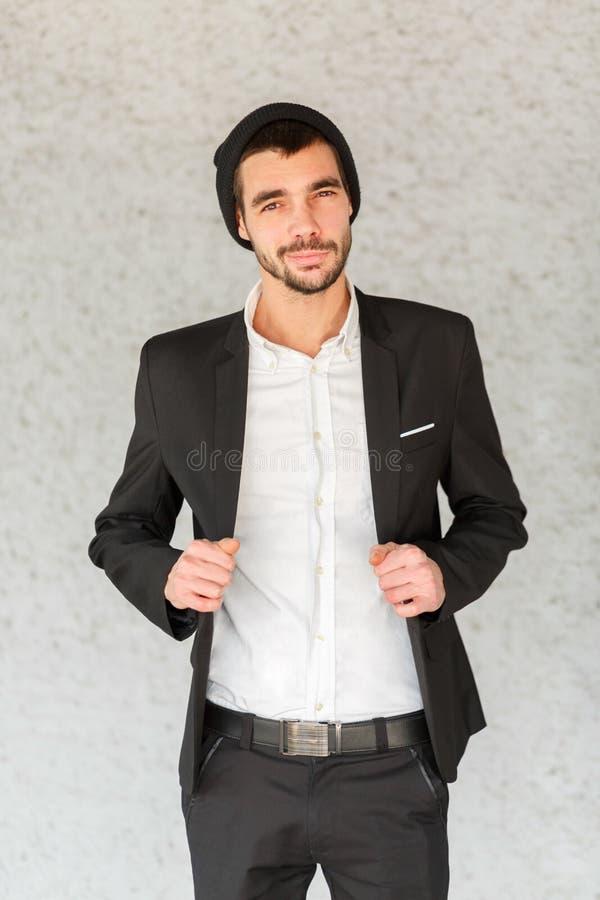 Un jeune homme d'affaires ajuste un costume noir sur un fond gris photo libre de droits