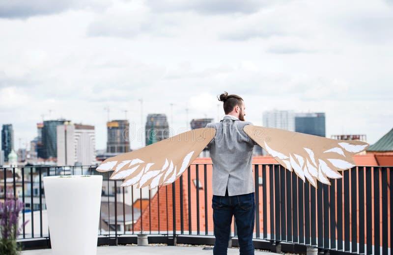 Un jeune homme d'affaires avec des ailes se tenant sur une terrasse, concept volant de m?taphore image stock