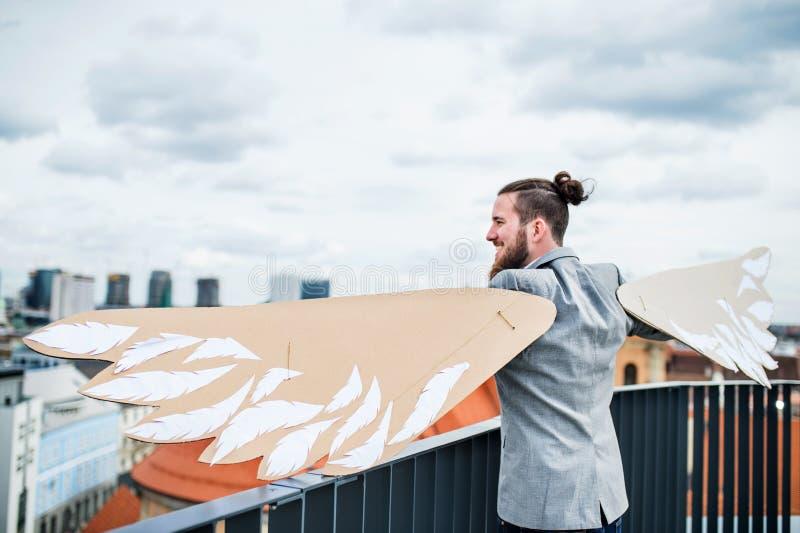 Un jeune homme d'affaires avec des ailes se tenant sur une terrasse, concept volant de m?taphore images libres de droits