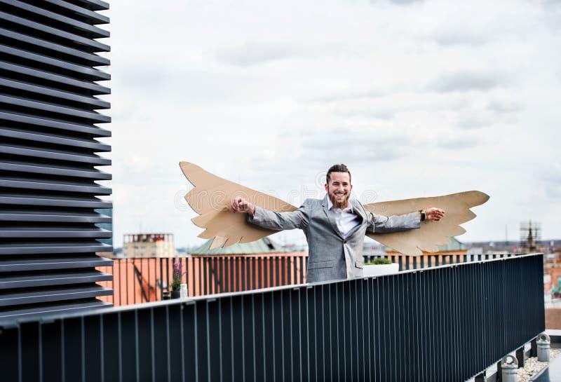 Un jeune homme d'affaires avec des ailes se tenant sur une terrasse, concept volant de m?taphore images stock