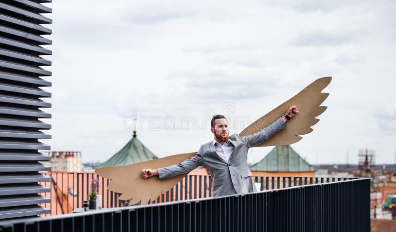 Un jeune homme d'affaires avec des ailes se tenant sur une terrasse, concept volant de m?taphore photo libre de droits