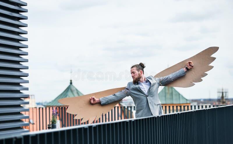Un jeune homme d'affaires avec des ailes se tenant sur une terrasse, concept volant de m?taphore image libre de droits