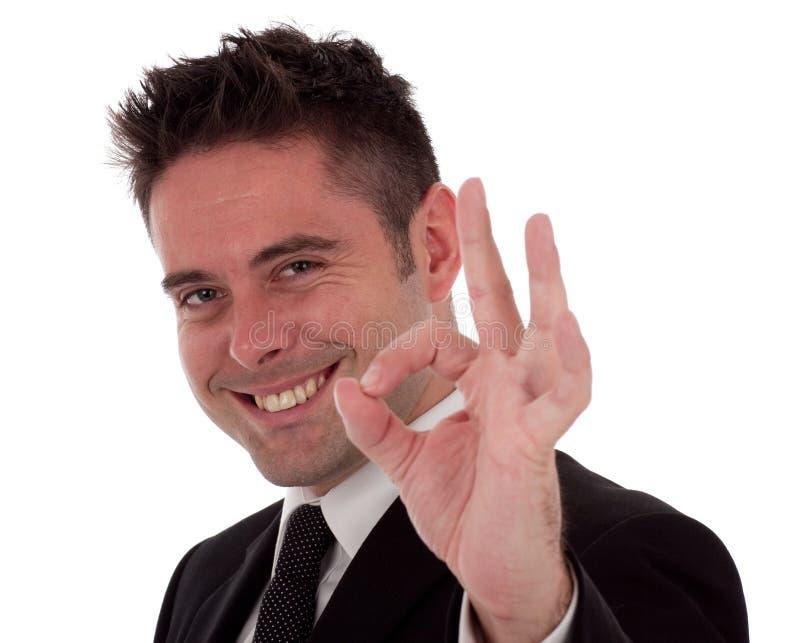 Un jeune homme d'affaires donne le signe en bon état image stock