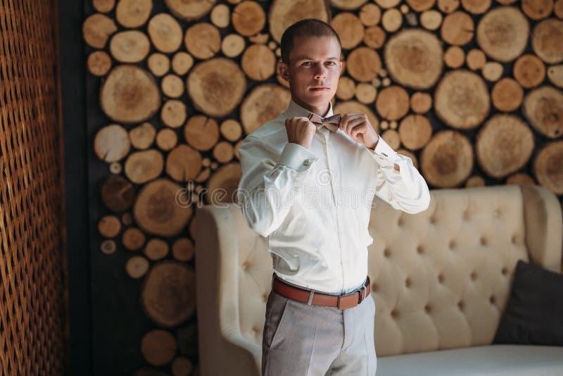 Un jeune homme d'affaires masculin obtient s'est habillé pour le travail Un type blond dans une chemise blanche essaye sur un noe photo stock