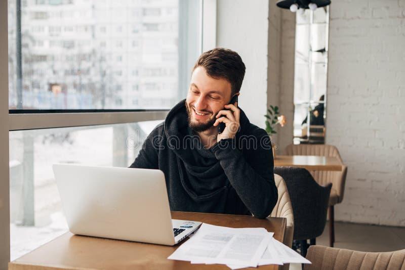 Un jeune homme d'affaires parlant au téléphone et travaillant à un ordinateur portable dans un café photographie stock libre de droits