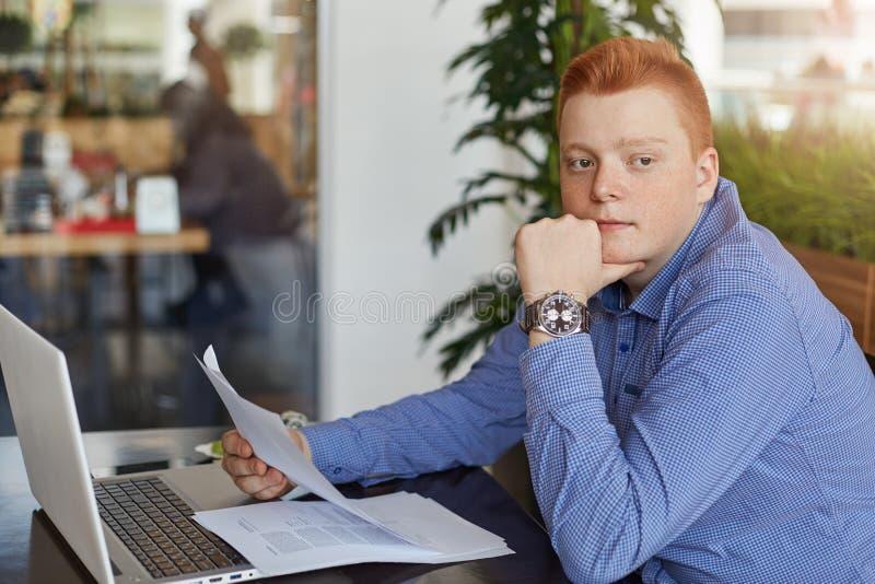 Un jeune homme d'affaires roux songeur utilisant la chemise formelle se reposant à la table avec l'ordinateur portable et aux doc images stock