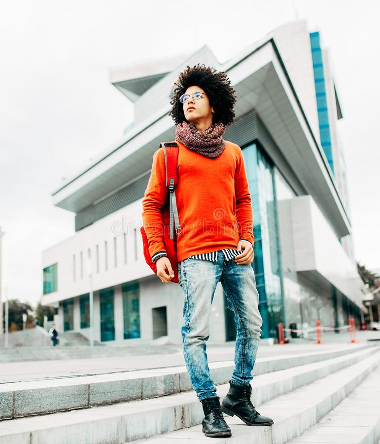 Un jeune homme d'Afro-américain avec backpackwalking rouge dans la ville images libres de droits