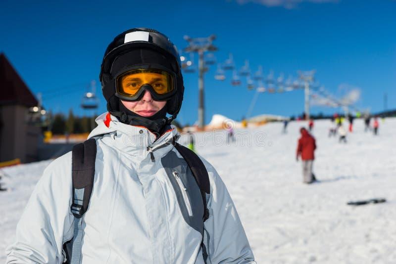 Un jeune homme dans le costume de ski, avec le casque et les lunettes de ski se tenant dedans image libre de droits