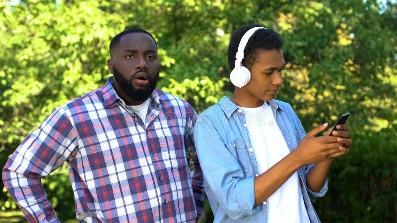 Un jeune homme dans les écouteurs avec son smartphone ignorant l'âge de la puberté de son père mécontent images stock