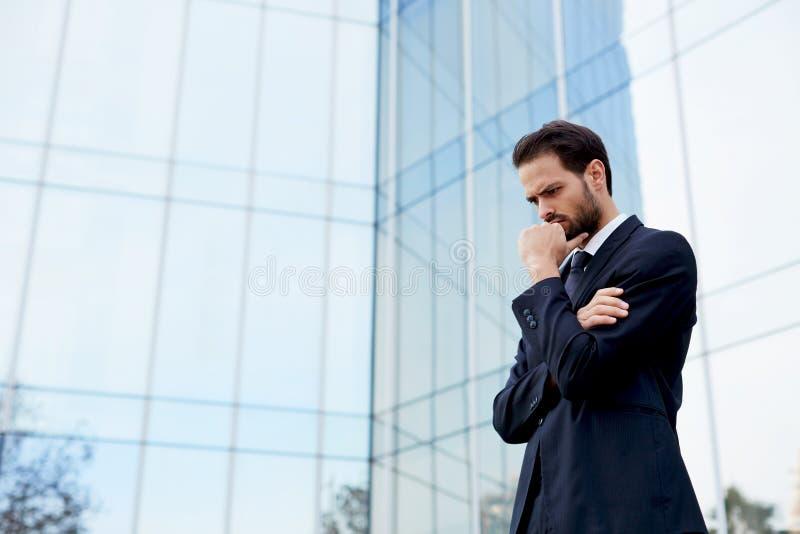 Un jeune homme dans un costume élégant se tenant près du bureau d'un bâtiment moderne photographie stock