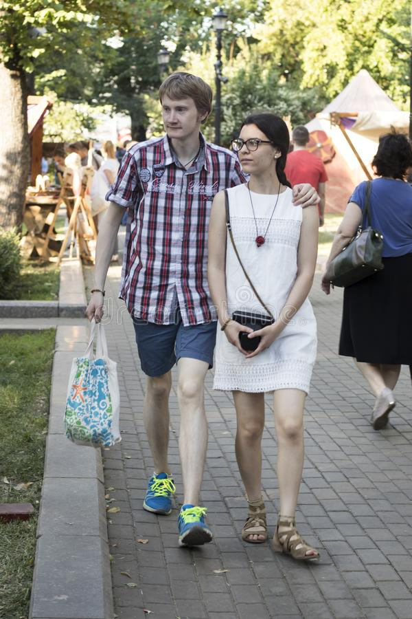 Un jeune homme dans une chemise de plaid et une fille dans une robe blanche s'embrassant descendent la rue image libre de droits