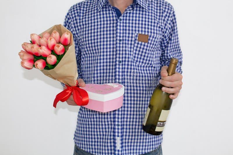 Un jeune homme dans une chemise et des jeans de plaid bleue, tenant un bouquet des tulipes, un boîte-cadeau en forme de coeur et  photo stock