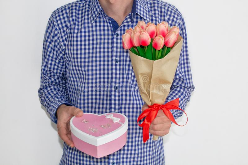 Un jeune homme dans une chemise et des jeans de plaid bleue, tenant un bouquet des tulipes et d'un boîte-cadeau sous forme de coe photo stock