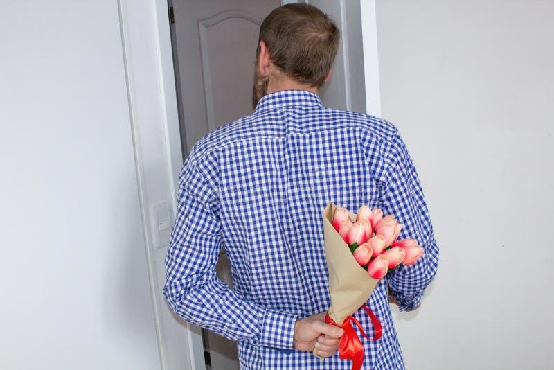 Un jeune homme dans une chemise et des jeans de plaid bleue, tenant un bouquet des tulipes derrière le sien de retour, et des cou image stock