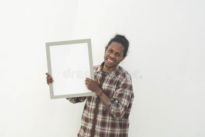 Un jeune homme de couleur tenant le conseil blanc avec le fond d'isolement dans le blanc image stock