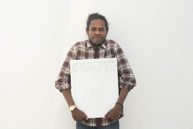 Un jeune homme de couleur tenant le conseil blanc avec le fond d'isolement dans le blanc photo libre de droits