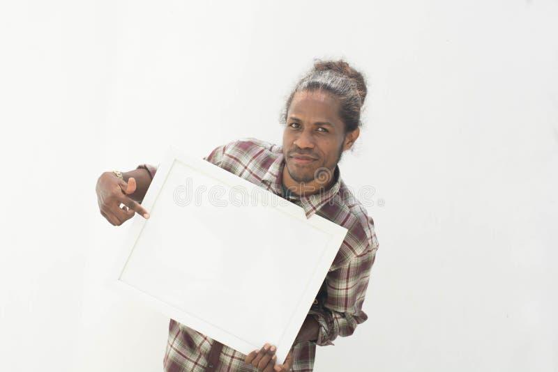 Un jeune homme de couleur tenant le conseil blanc avec le fond d'isolement dans le blanc photographie stock libre de droits