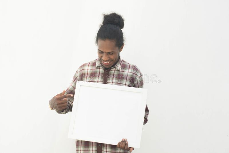 Un jeune homme de couleur tenant le conseil blanc avec le fond d'isolement dans le conseil blanc blanc et vide pour votre concept photographie stock