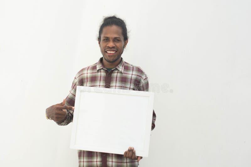 Un jeune homme de couleur tenant le conseil blanc vide avec le fond d'isolement dans blanc, concept de signe images libres de droits