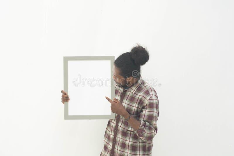 Un jeune homme de couleur tenant le conseil blanc vide avec le fond d'isolement dans le blanc photographie stock libre de droits