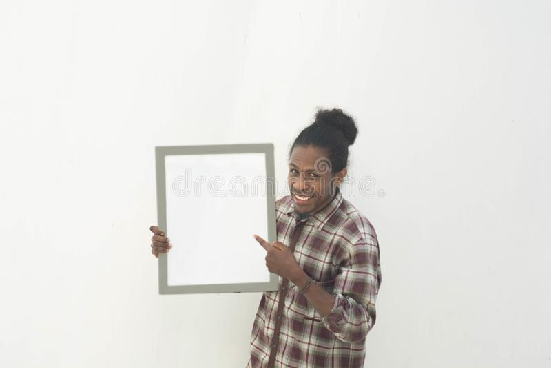Un jeune homme de couleur tenant le conseil blanc vide avec le fond d'isolement dans le blanc photo stock