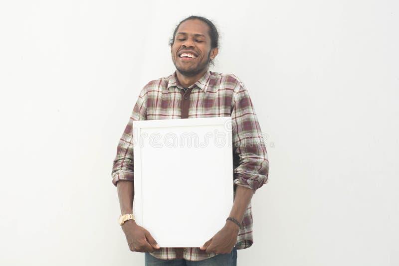 Un jeune homme de couleur tenant le conseil blanc vide avec le fond d'isolement en Afrique blanche et souriante Amérique tenant l photographie stock libre de droits