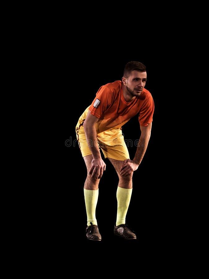 Un jeune homme de joueur de football du football sur le fond noir photographie stock