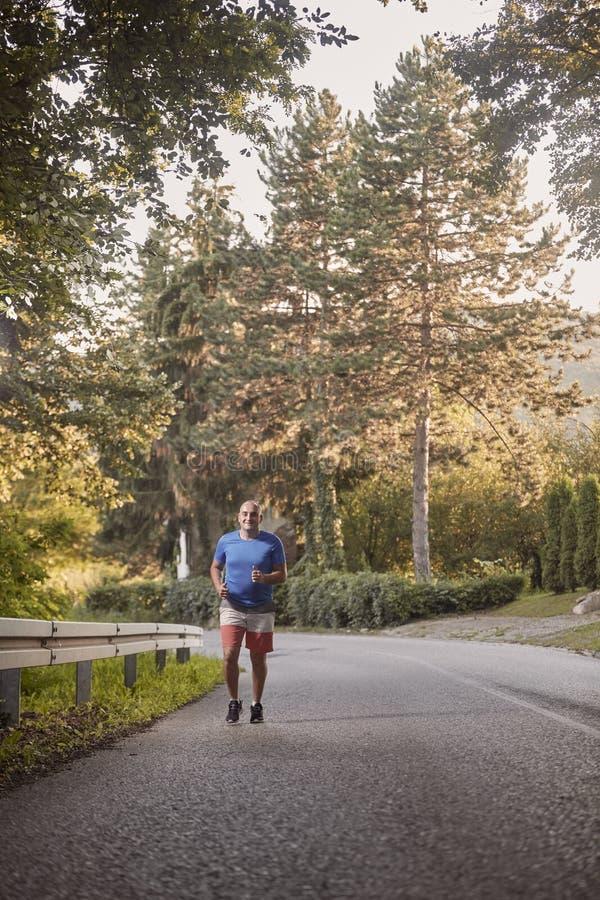 Un jeune homme de poids excessif, dehors nature, fonctionnant sur la route goudronnée images libres de droits