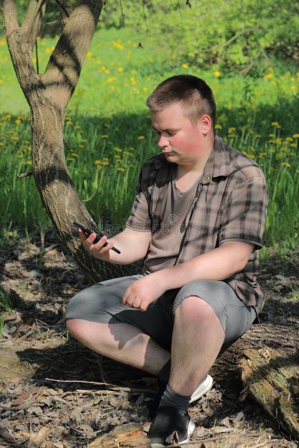 Un jeune homme dodu s'assied sur un tronc d'arbre Dans la perspective d'un pré avec les pissenlits de floraison Tient un smartpho image stock