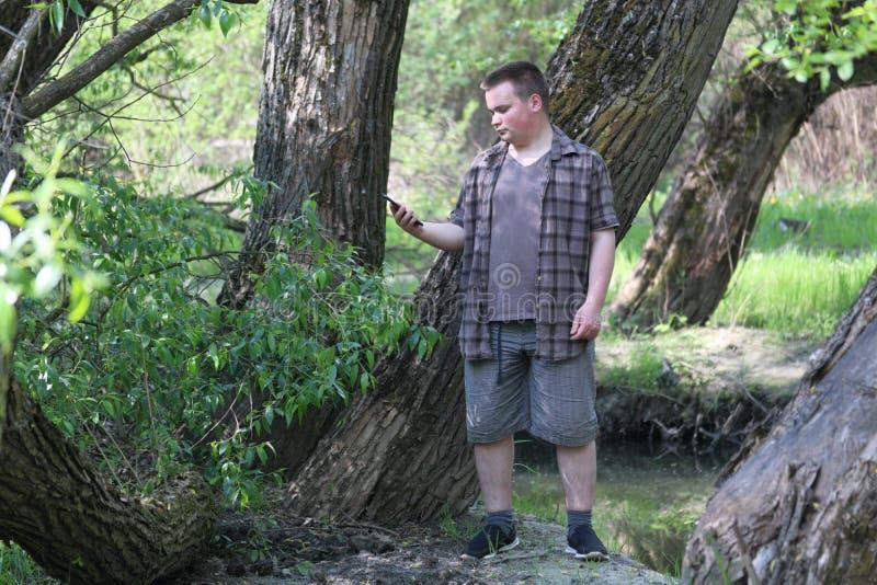 Un jeune homme dodu se tient pr?s d'un arbre Tient un smartphone dans sa main Regarder d'un air songeur l'instrument images stock