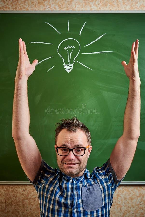 Un jeune homme en désordre avec des verres tient ses mains sur le fond d'un tableau vert photos stock