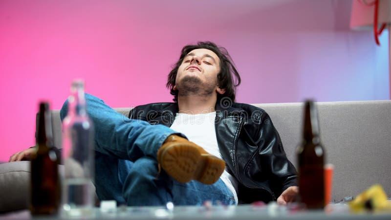 Un jeune homme enivré se reposant sur un canapé, des bouteilles d'alcool sur la table, une fête étudiante photos libres de droits