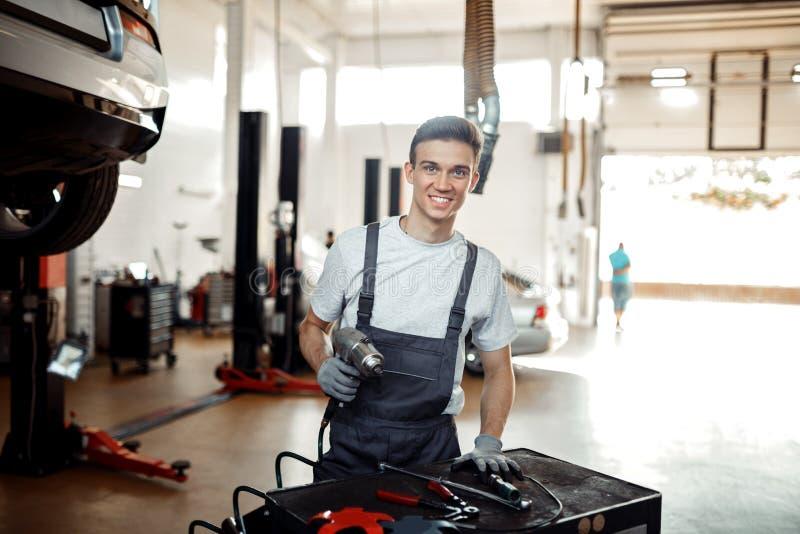 Un jeune homme est au travail tout en se préparant à changer un pneu photo libre de droits