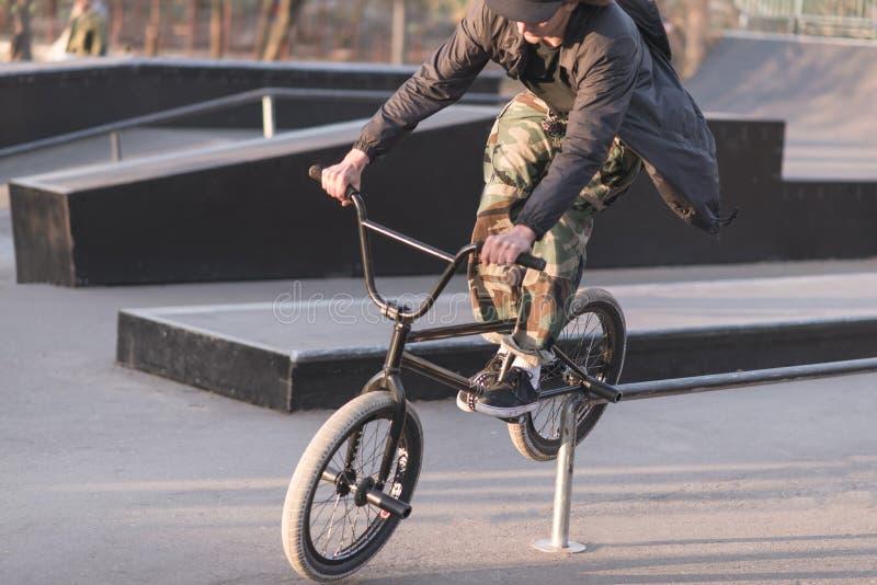Un jeune homme est exécute le tour sur le BMX dans un vélo Glissement sur des rails sur BMX photographie stock
