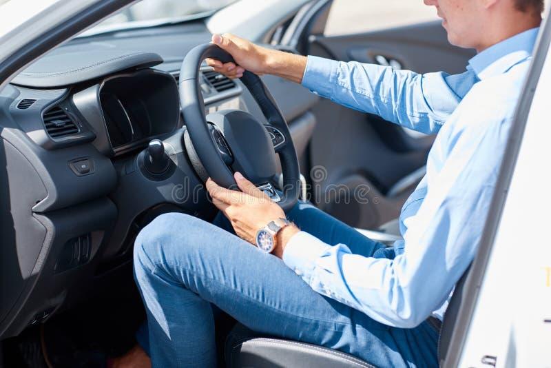 Un jeune homme est venu chez le salon de l'Auto pour choisir une nouvelle voiture photos stock