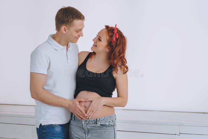 Un jeune homme et une belle jeune femme, recherchent le ventre En prévision du bébé Femme rousse enceinte Coeur images libres de droits