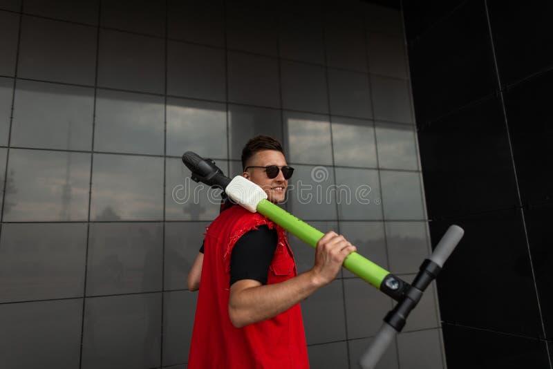 Un jeune homme heureux hipster se tient debout avec un scooter sur l'épaule Joli gars joyeux avec le sourire en vêtements de jean images stock