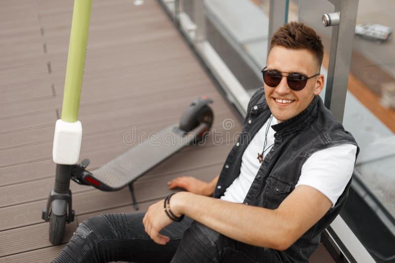 Un jeune homme joyeux en hipster dans un gilet denim en jeans gris en lunettes de soleil repose sur un plancher en bois sur la te photographie stock