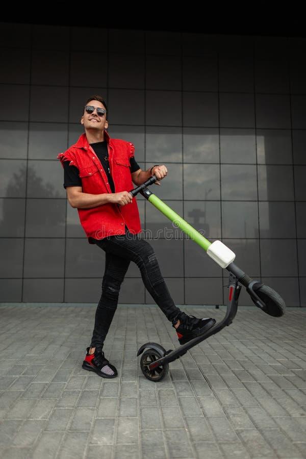 Un jeune homme joyeux et coiffé de vêtements denim rouge-noir dans des lunettes de soleil pose avec un scooter électrique moderne photo stock