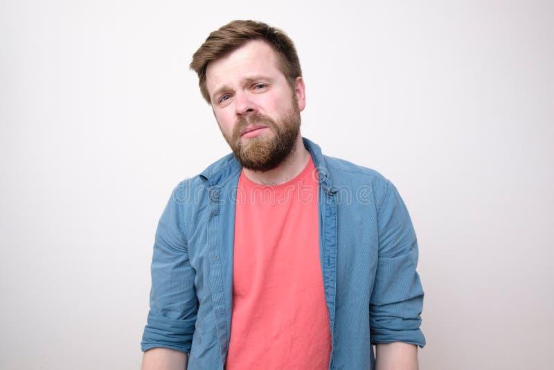 Un jeune homme las et torturé qui a un mal de tête regarde tristement avec les yeux rétrécis Sur le fond blanc photos libres de droits