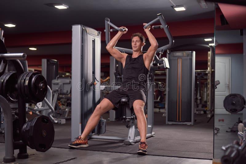 Un jeune homme, machine de forme physique, lat de dos posé abaissent, foncé photo stock