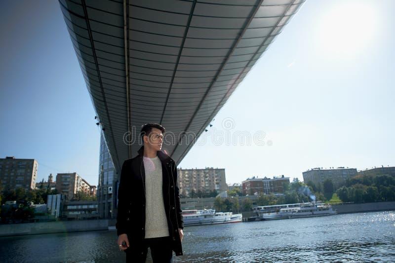 Un jeune homme, mince Avec les cheveux foncés et les yeux bruns En se tenant sous le pont à la rivière, regardez l'appareil-photo images stock
