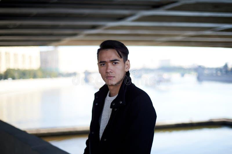 Un jeune homme, mince Avec les cheveux foncés et les yeux bruns En se tenant sous le pont à la rivière, regardez l'appareil-photo image stock