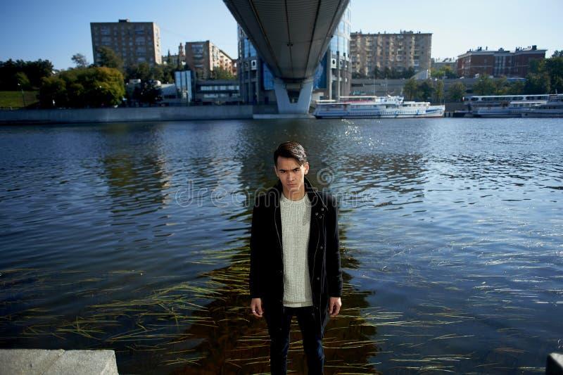 Un jeune homme, mince Avec les cheveux foncés et les yeux bruns En se tenant sous le pont à la rivière, regardez l'appareil-photo photographie stock libre de droits