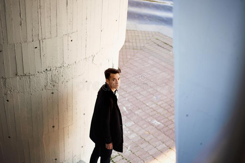 Un jeune homme, mince Avec les cheveux foncés et les yeux bruns Se tenant sous un pont à côté de la rivière, les mains ont croisé photo stock