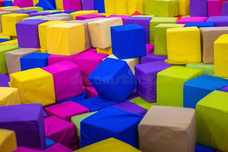 Un jeune homme ou un garçon, père jouant et sautant en cubes mous dans la piscine sèche de la salle du ` s d'enfants de jeu pour  photographie stock libre de droits