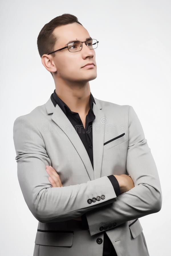 Un jeune homme portant un costume gris et des lunettes photos stock