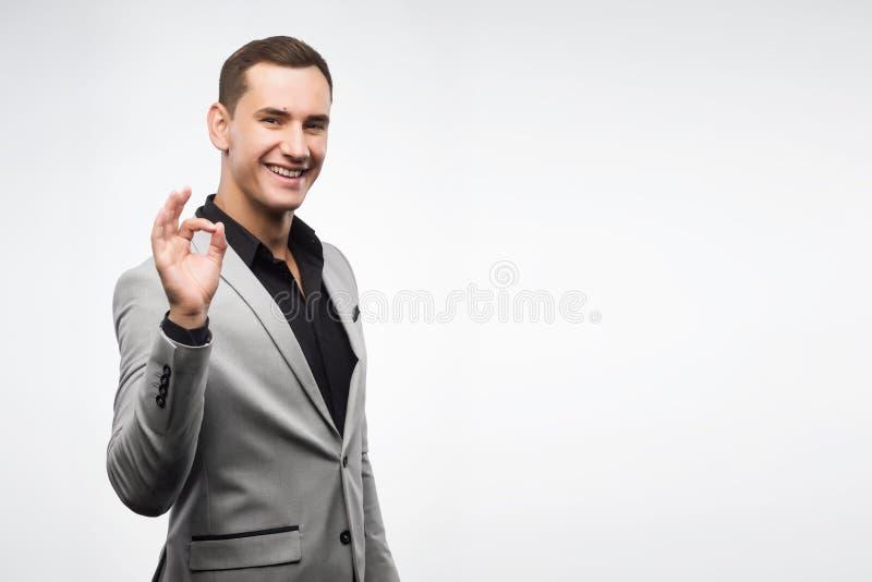 Un jeune homme portant un costume gris montre un ok de signe images stock