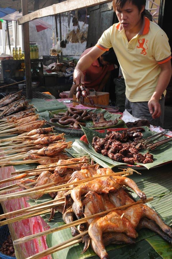Un jeune homme préparant les poissons et la viande grillés au marché de la ville de Luang Prabang photographie stock